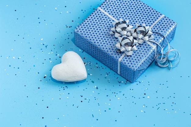 Geschenkdoos verpakt in blauw papier op blauw.