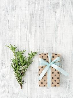 Geschenkdoos verpakt in bruin papier en takje op witte houten tafel, kopie ruimte.