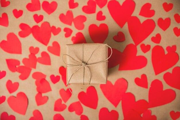 Geschenkdoos verpakt in kraftpapier omgeven door rode harten op bruin gewoon papier