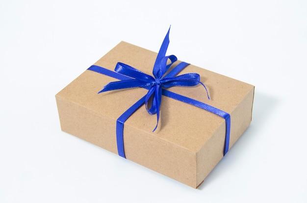 Geschenkdoos verpakt in kraftpapier, vastgebonden met snoepgoed kersttouw op donkerblauwe achtergrond