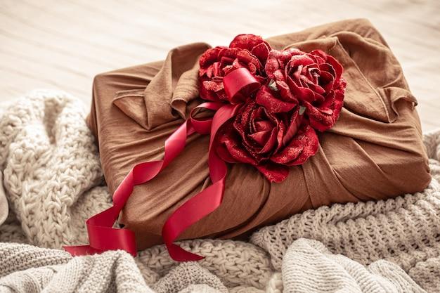 Geschenkdoos versierd met linten en decoratieve rozen op gebreide artikelen. originele cadeauverpakking voor valentijnsdag.