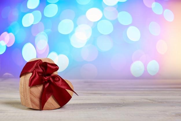 Geschenkdoos voor ringen. houten kist hart met lint strik op onscherpe achtergrond. wenskaart