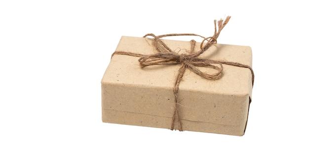 Geschenkdoos wrap met bruin gerecycled papier en touw geïsoleerd op wit met uitknippad