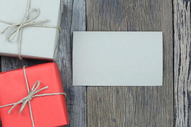 Geschenkdozen en blanco papier op houten vloer.