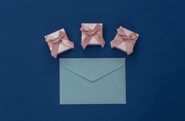 Geschenkdozen en enveloppen op klassieke blauwe achtergrond. kleur 2020. bovenaanzicht