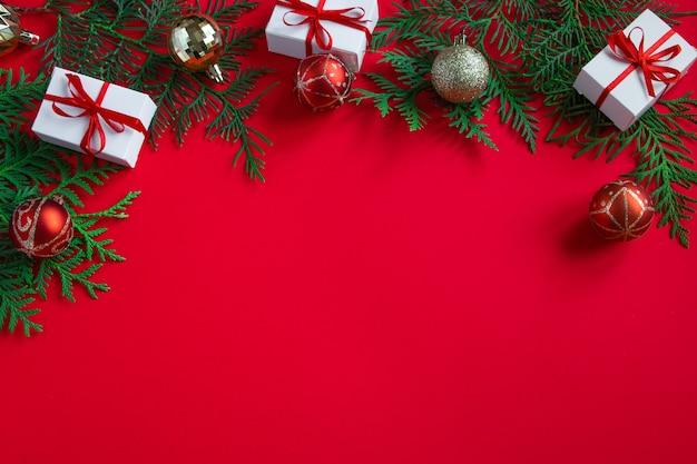 Geschenkdozen en feestelijk decor. kerstcompositie op rode achtergrond. plaats voor tekst.