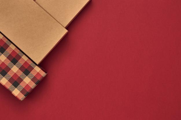 Geschenkdozen en gave tas op een rode achtergrond. zwarte vrijdag. ruimte kopiëren, plat leggen, mock-up, bovenaanzicht.