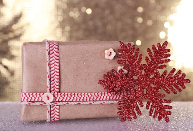 Geschenkdozen en kerstboom speelgoed op tafel op glanzende achtergrond Premium Foto