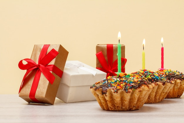 Geschenkdozen en smakelijke verjaardagsmuffins met chocoladeglazuur en karamel, versierd met brandende feestelijke kaarsen op houten en beige achtergrond. gelukkig verjaardagsconcept.