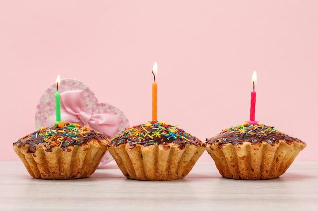 Geschenkdozen en smakelijke verjaardagsmuffins met chocoladeglazuur en karamel, versierd met brandende feestelijke kaarsen op houten en roze achtergrond. gelukkig verjaardagsconcept.