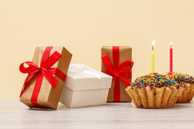 Geschenkdozen en smakelijke verjaardagsmuffins, versierd met brandende feestelijke kaarsen op houten en beige achtergrond. gelukkig verjaardagsconcept.