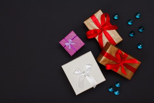 Geschenkdozen gebonden met linten en glazen bollen op zwarte achtergrond. wenskaart concept. bovenaanzicht met kopie ruimte.