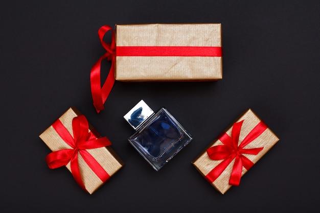 Geschenkdozen gebonden met rode linten en fles parfum op zwarte achtergrond. wenskaart concept. bovenaanzicht.
