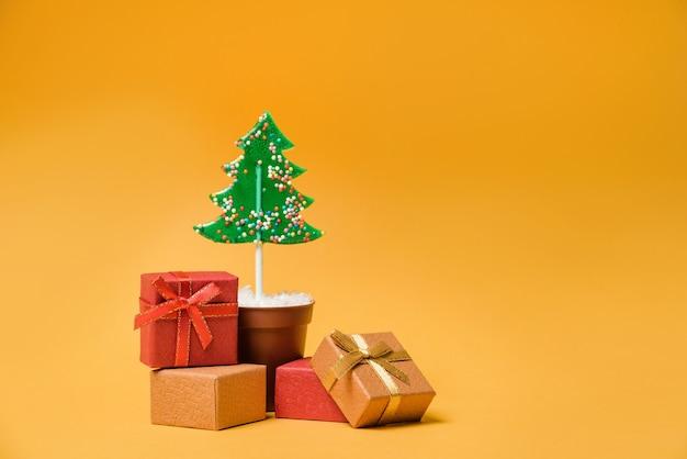 Geschenkdozen in de buurt van de kerstboom, op een gele achtergrond met kopie ruimte. lollipop in de vorm van een kerstboom in een bloempot met kerstcadeaus.