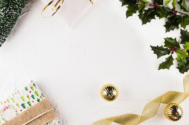 Geschenkdozen in de buurt van kerstballen en lint
