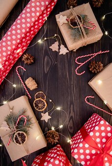 Geschenkdozen in knutselpapier versierd met dennenappels, zuurstokken en dennentakken