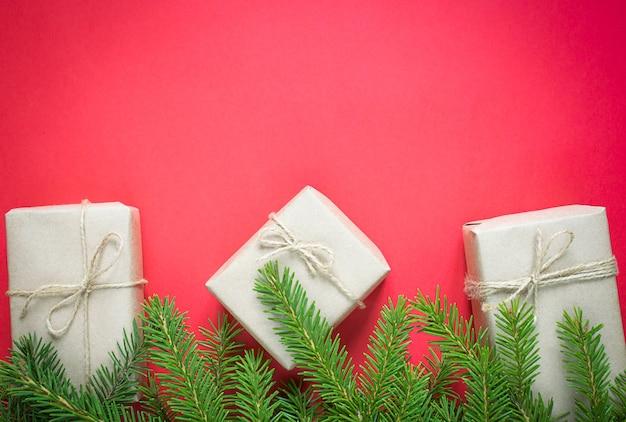 Geschenkdozen in kraft papier met dennentakken op een rode achtergrond. ecovriendelijk kerstconcept.