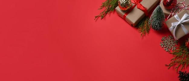 Geschenkdozen, kerstversieringen en sparrentakken op rode achtergrond. ruimte kopiëren.