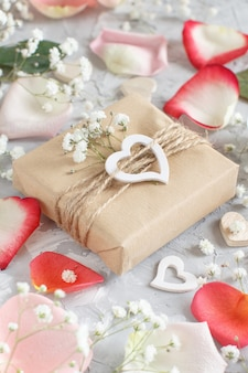 Geschenkdozen met bloemen en harten op een grijze achtergrond