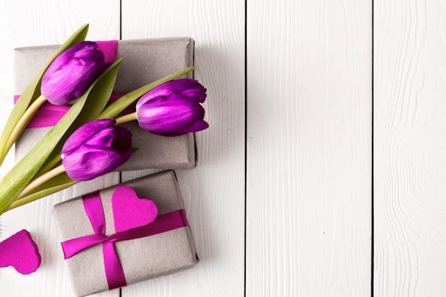 Geschenkdozen met bloemen op witte houten muur