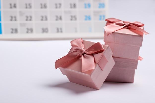 Geschenkdozen met desktopkalender op witte achtergrond. vakantie winkelen, zwarte vrijdag, maandelijks speciale aanbieding-concept