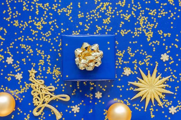 Geschenkdozen met een gouden boog en dennenboom met kerstballen op een blauwe achtergrond, gouden glimmende glitter sterren op een blauwe achtergrond, kerstmis concept, plat lag, bovenaanzicht