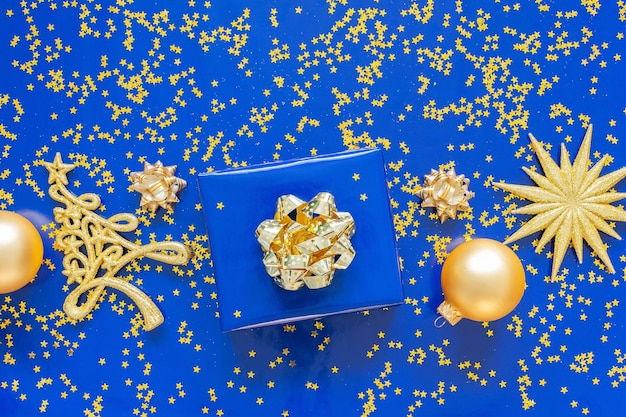 Geschenkdozen met een gouden boog en dennenboom met kerstballen op een blauwe achtergrond, gouden glimmende glitter sterren op een blauwe achtergrond