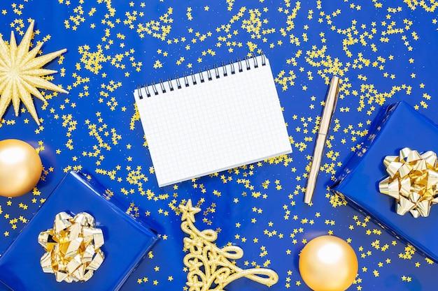 Geschenkdozen met een gouden boog en dennenboom met kerstballen op een blauwe achtergrond, gouden glimmende glitter sterren, open spiraal kladblok en pen, plat leggen, bovenaanzicht