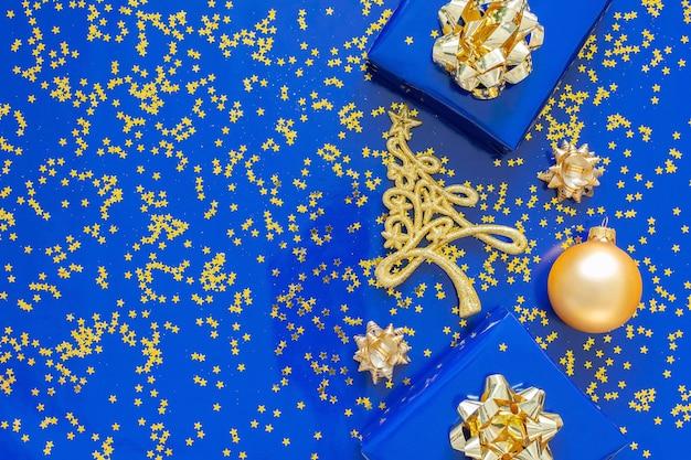 Geschenkdozen met een gouden boog en dennenboom met kerstballen op een blauwe achtergrond