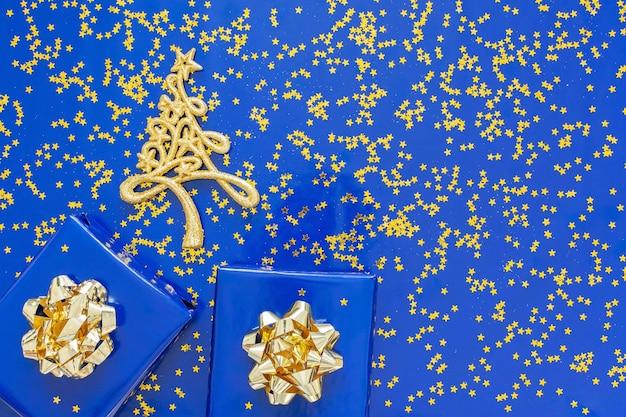 Geschenkdozen met een gouden boog en dennenboom op een blauwe muur, gouden glimmende glitter sterren op een blauwe muur, kerst concept, plat leggen, bovenaanzicht