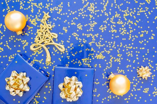 Geschenkdozen met een gouden strik en dennenboom met kerstballen op een blauwe, gouden glimmende glittersterren