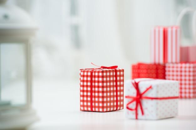 Geschenkdozen met kerstcadeautjes verpakt in rood papier met ornament. veel copyspace