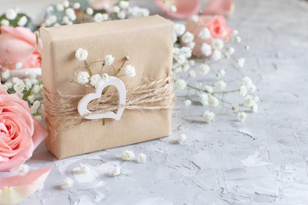 Geschenkdozen met kleine witte bloemen en harten op een grijze achtergrond