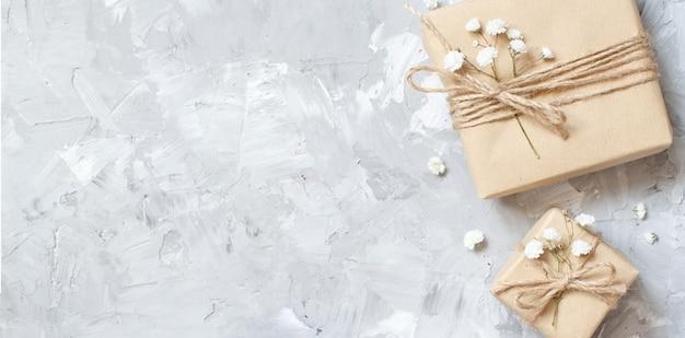 Geschenkdozen met kleine witte bloemen op een grijze achtergrond
