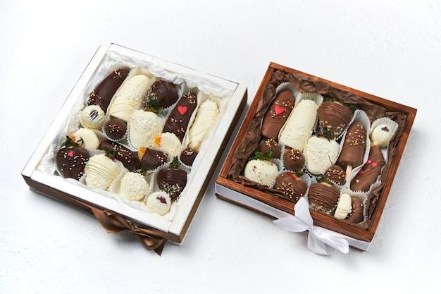 Geschenkdozen met rijp fruit bedekten de witte en donkere chocolade