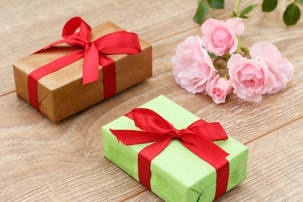 Geschenkdozen met rode linten en mooie roze rozen op de houten planken. concept van het geven van een geschenk op feestdagen. bovenaanzicht.