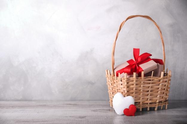 Geschenkdozen met rode linten op een mand en twee harten