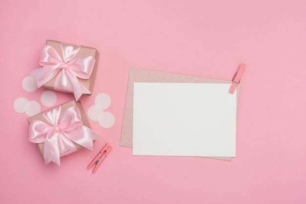 Geschenkdozen met roze strik en lege wenskaart op pastel roze tafel.