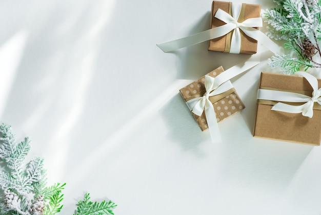Geschenkdozen met sneeuw fir takken en zonlichtstralen. kerstkaart. plat lag copyspace