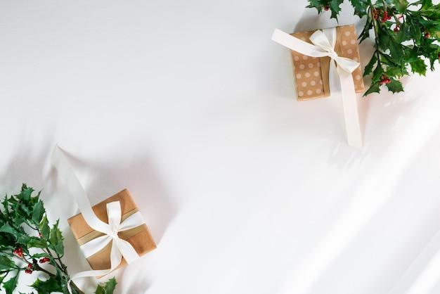 Geschenkdozen met sneeuw hulsttakken en zonlichtstralen. kerstkaart. plat lag copyspace