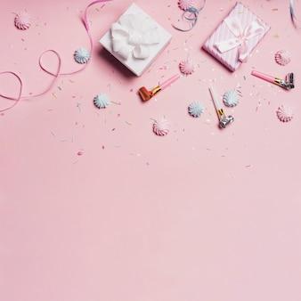 Geschenkdozen met snoepjes en partijblazers op roze achtergrond