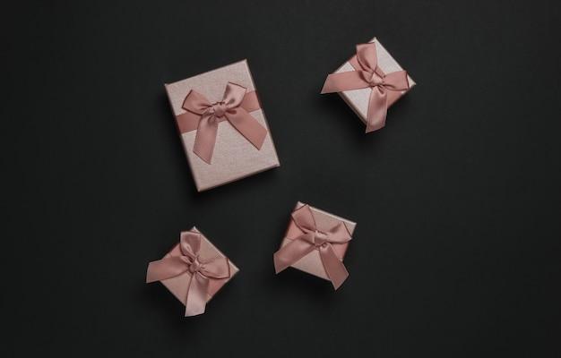 Geschenkdozen met strik op zwarte achtergrond. compositie voor kerstmis, black friday, verjaardag of bruiloft.
