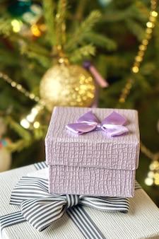 Geschenkdozen met strikken op de deksels onder een kerstboom op oudejaarsavond