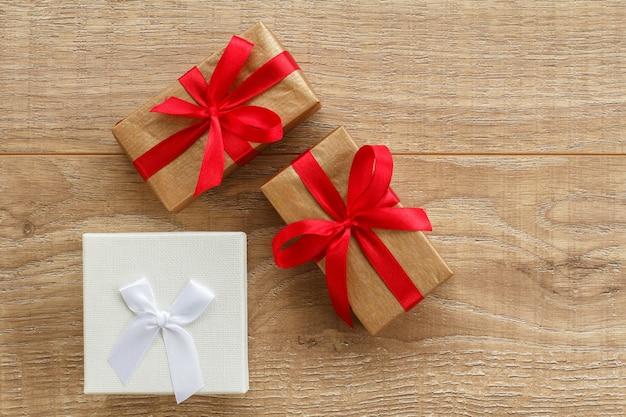 Geschenkdozen met witte en rode linten op houten planken. wenskaart concept. bovenaanzicht.