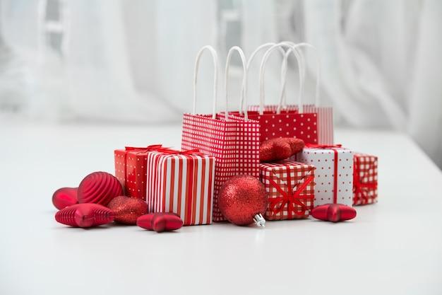 Geschenkdozen met xmas presenteert verpakt in rood papier met ornament op lichte interieur achtergrond