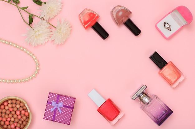 Geschenkdozen, poeder, nagellak, flesje parfum en bloemen op een roze achtergrond. vrouwen cosmetica en accessoires. bovenaanzicht.