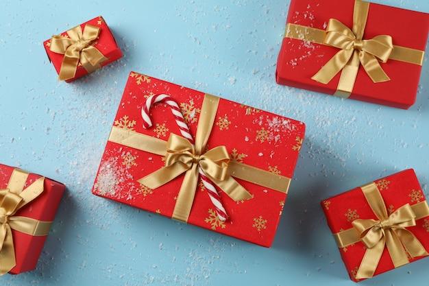 Geschenkdozen, riet van het suikergoed en sneeuw op blauwe achtergrond, bovenaanzicht