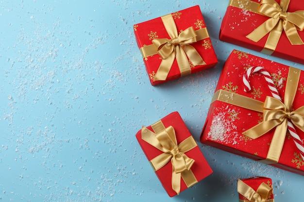 Geschenkdozen, riet van het suikergoed en sneeuw op blauwe achtergrond, kopie ruimte