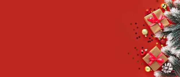 Geschenkdozen, sparrentakken en rode en gouden ballen op rood oppervlak