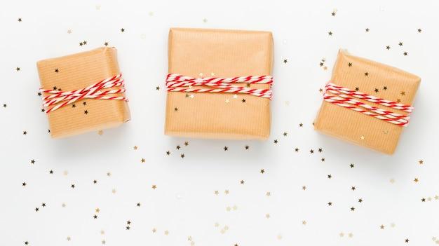 Geschenkdozen verpakt in ambachtelijk papier met gouden sterren op witte achtergrond